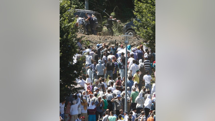 Members of the Serbian delegation, top, including Serbia's Prime Minister Aleksandar Vucic, unseen, flee from the baying crowd during a scuffle at the Potocari memorial complex near Srebrenica, 150 kilometers northeast of Sarajevo, Bosnia and Herzegovina, Saturday, July 11, 2015. Vucic and his delegation was forced to flee after hundreds of people that gathered to commemorate the 20th anniversary of the Srebrenica massacre hurled stones, water bottles and insults at him.(AP Photo/Amel Emric)