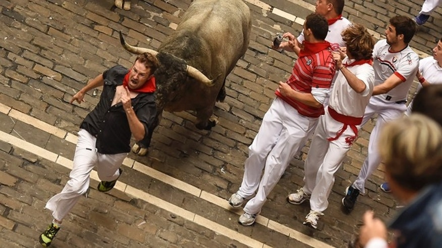 A participant runs in front of a ''Jose Escolar Gil'' fighting bull alongside Mercaderes street, during the fifth running of the bulls, at the San Fermin Festival, in Pamplona, Spain, Saturday, July 11, 2015. Revelers from around the world arrive to Pamplona every year to take part in some of the eight days of the running of the bulls. (AP Photo/Alvaro Barrientos)