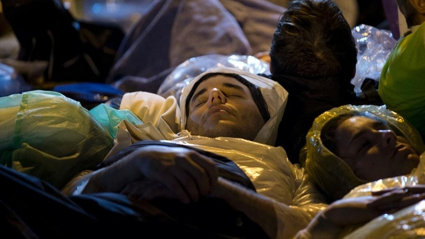 A couple sleeps on the street as they wait for the Mass to be celebrated by Pope Francis, in Caacupe, Paraguay, Friday, July 10, 2015. While in Paraguay, Francis will celebrate two Masses, including one in Caacupe on Saturday, the center of Paraguayan spirituality. (AP Photo/Natacha Pisarenko)