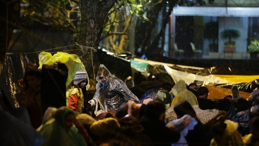 Pilgrims wear rain ponchos during a night vigil as they wait for the Mass to be celebrated by Pope Francis, in Caacupe, Paraguay, Friday, July 10, 2015. While in Paraguay, Francis will celebrate two Masses, including one in Caacupe on Saturday, the center of Paraguayan spirituality. (AP Photo/Jorge Saenz)