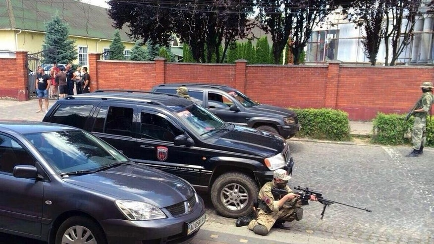 Armed activists of the nationalist militia Right Sector  take position in the site of unrest in Mukhachevo, Western Ukraine,  Saturday, July 11, 2015. At least two people were killed Saturday in a gun and grenade attack in a western Ukraine city involving the country's notorious nationalist militia Right Sector. The violence in the city of Mukhachevo, near the Polish and Hungarian borders, broke out at a sports facility reportedly controlled by a national parliament member from a faction opposed to Right Sector. (AP Photo)