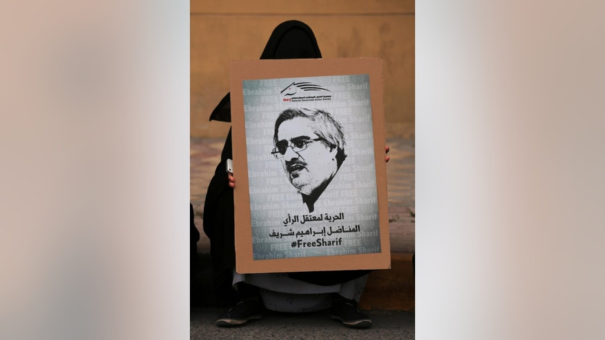 "FILE- in this Friday, March 21, 2014 file photo, A Bahraini pro-democracy protester holds a poster with image of jailed Bahraini political leader Ibrahim Sharif as she waits for a march to start in Abu Saiba, west of the capital of Manama, Bahrain. Bahraini authorities say they have arrested a top opposition leader less than a month after he was freed from prison. The Interior Ministry announced the arrest of former National Democratic Action Society head Sharif on its Twitter feed early Sunday, July 12, 2015 saying he was detained for ""violating the law. (AP Photo/Hasan Jamali, File)"