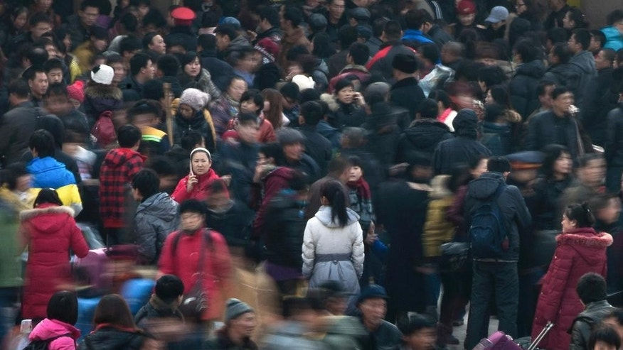FILE - In this Jan. 8, 2012 file photo, people rush to catch their train at Beijing station in Beijing, China as millions of Chinese are expected to cramp onto China's train network in the coming weeks to return home for the Chinese lunar new year. Beijing's city government said Sunday, July 12, 2015 that it is going to move part of its administrative functions out of the city center as part of a plan to better integrate the Chinese capital with its surrounding areas. The municipal government's Communist Party committee also agreed at a meeting Friday and Saturday to stick to its target to limit Beijing's population to 23 million, according to the government's information office microblog. Its population was 21.5 million at the end of 2014. (AP Photo/Andy Wong, File)