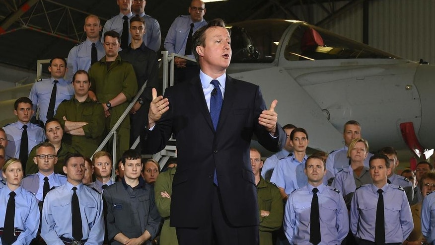 "Britain's Prime Minister David Cameron addresses Royal Air Force airmen and officers during a visit to RAF Coningsby England Monday July 13, 2015. Britain's military should invest more in drones and elite troops to help counter the threat from the Islamic State group, Prime Minister David Cameron said Monday, calling terrorism one of the ""evolving threats"" facing the U.K. (Joe Giddens/PA via AP) UNITED KINGDOM OUT"