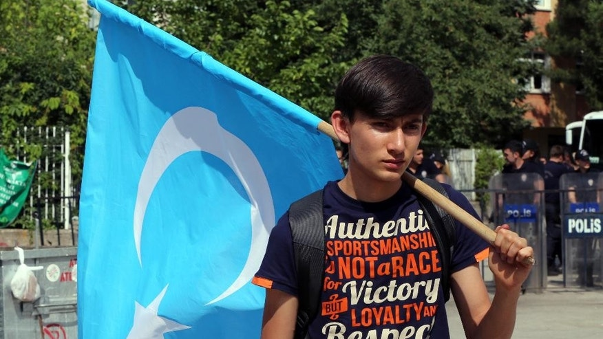 An Uighur boy carries a flag of  East Turkestan, the term separatist Uighurs and Turks use to refer to the Uighurs' homeland in China's Xinjiang region,after the riot police used pepper spray to push back a group of Uighur protesters who try to break through a barricade outside the Chinese Embassy in Ankara, Turkey, Thursday, June 9. 2015. Thailand sent back to China more than 100 ethnic Uighur refugees on Thursday, drawing harsh criticism from the U.N. refugee agency and human rights groups over concerns that they face persecution by the Chinese government. Protesters in Turkey, which accepted an earlier batch of Uighur refugees from Thailand, ransacked the Thai Consulate in Istanbul overnight.(AP Photo/Burhan Ozbilici)