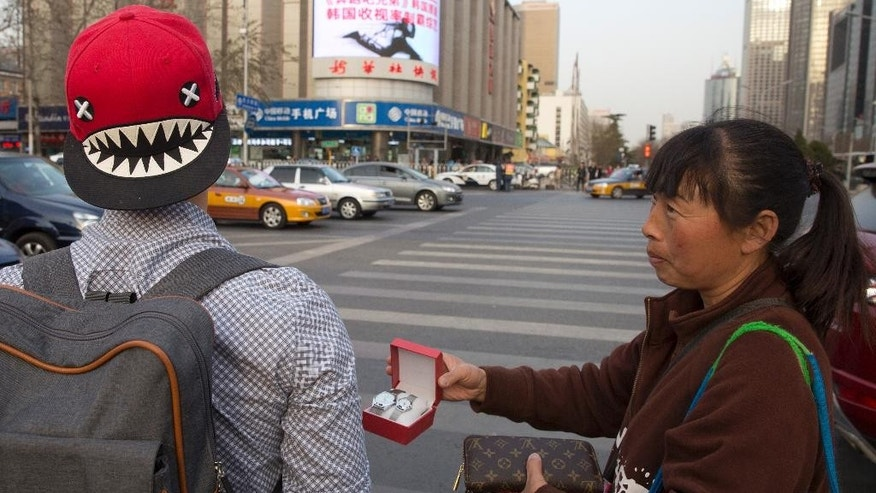 In this photo taken Friday, March 20, 2015, a street vendor hawks counterfeit branded items to tourists on the streets of Beijing. Counterfeiting is a big business, by one estimate, the global market for fakes will hit $1.7 trillion this year. (AP Photo/Ng Han Guan)