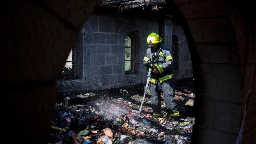 FILE - In this Thursday, June 18, 2015 file photo, an Israeli firefighter works at the site of a fire that caused heavy damage to the Church of the Multiplication of the Loaves and Fish after an arson attack overnight on the shore of the Sea of Galilee in Tabgha, northern Israel. Israeli police said on Sunday, July 12, 2015, that they have arrested a number of suspects, without elaborating on their identity, in last month's arson attack on the  Catholic church. The fire is believed to be an attack by Jewish extremists on one of the most popular stops for Christian pilgrims visiting the Holy Land. (AP Photo/Ariel Schalit, File)