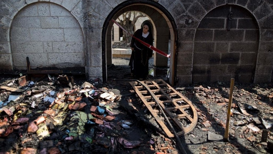 FILE - In this Thursday, June 18, 2015 file photo, a nun looks at damage to the Church of the Multiplication of the Loaves and Fish after an arson attack overnight on the shore of the Sea of Galilee in Tabgha, northern Israel. Israeli police said on Sunday, July 12, 2015, that they have arrested a number of suspects, without elaborating on their identity, in last month's arson attack on the  Catholic church. The fire is believed to be an attack by Jewish extremists on one of the most popular stops for Christian pilgrims visiting the Holy Land. (AP Photo/Ariel Schalit, File)
