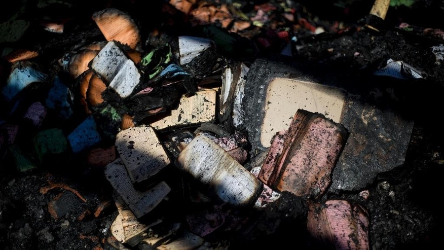 FILE - In this Thursday, June 18, 2015 file photo, partially burnt prayer books and leaflets lay in the heavily damaged  Church of the Multiplication of the Loaves and Fish after an arson attack overnight on the shore of the Sea of Galilee in Tabgha, northern Israel. Israeli police said on Sunday, July 12, 2015, that they have arrested a number of suspects, without elaborating on their identity, in last month's arson attack on the  Catholic church. The fire is believed to be an attack by Jewish extremists on one of the most popular stops for Christian pilgrims visiting the Holy Land. (AP Photo/Ariel Schalit, File)