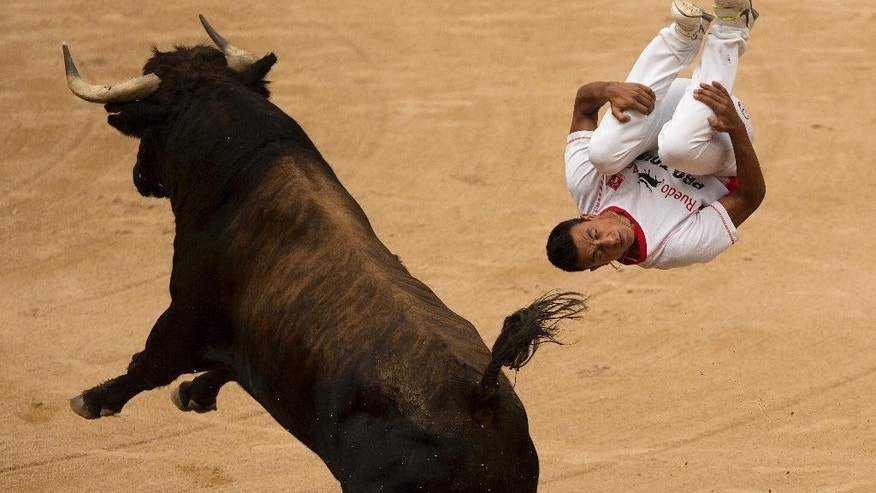 A ''recortador'' jumps over a bull during a competition at the San Fermin festival in Pamplona, Spain, Saturday, July 11, 2015. Revelers from around the world arrive in Pamplona every year to take part in some of the eight days of the running of the bulls. (AP Photo/Andres Kudacki)