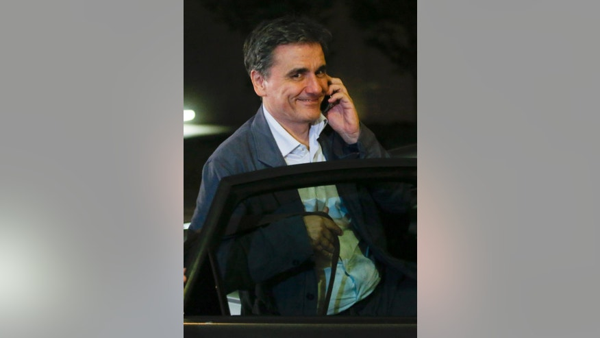 Greek Finance Minister Euclid Tsakalotos  leaves after a meeting of eurozone finance ministers at the EU Lex building in Brussels on Saturday, July 11, 2015. Greece's negotiators head to Brussels on Saturday armed with their reform proposals and parliamentary backing to seek a third bailout, but with the shadow of severe dissent from governing lawmakers hanging over them. (Olivier Hoslet/Pool Photo via AP)