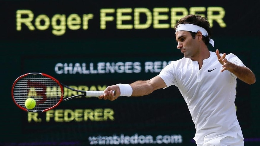 Roger Federer of Switzerland touches his face during the men's singles final against Novak Djokovic of Serbia at the All England Lawn Tennis Championships in Wimbledon, London, Sunday July 12, 2015. (Toby Melville/Pool Photo via AP)