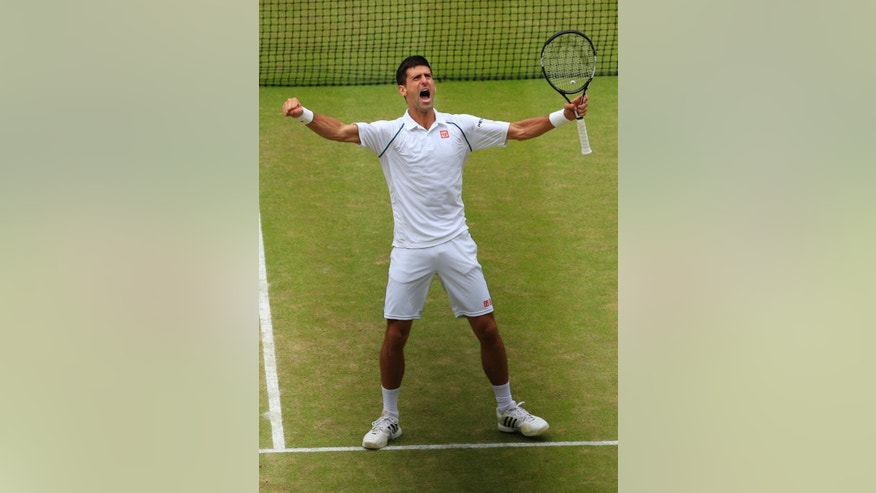 Novak Djokovic of Serbia celebrates winning the men's singles final against Roger Federer of Switzerland at the All England Lawn Tennis Championships in Wimbledon, London, Sunday July 12, 2015. Djokovic won the match 7-6, 6-7, 6-4, 6-3.  (Jonathan Brady/Pool Photo via AP)