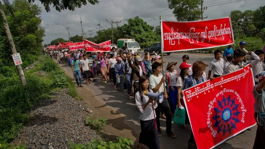 Myanmar factory workers march protesting against proposed minimum wage at Hlaingtharyar industrial zone, suburb of Yangon, Myanmar, Sunday, July 12, 2015. Several hundred workers in Myanmar staged a peaceful demonstration Sunday to demand that a new daily minimum wage be set higher than proposed. (AP Photo/Gemunu Amarasinghe)