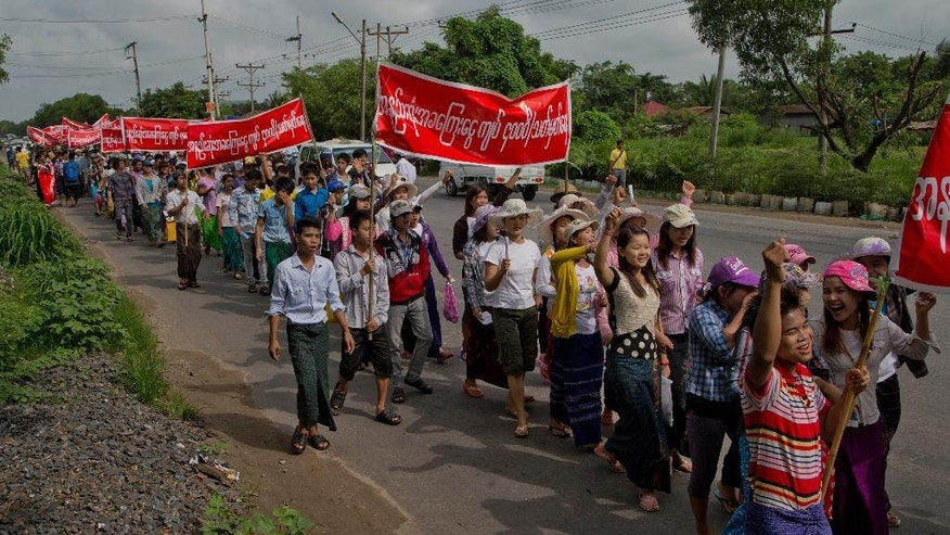 Myanmar factory workers shout slogans during a march against proposed minimum wage at Hlaingtharyar industrial zone, suburb of Yangon, Myanmar, Sunday, July 12, 2015. Several hundred workers in Myanmar staged a peaceful demonstration Sunday to demand that a new daily minimum wage be set higher than proposed. (AP Photo/Gemunu Amarasinghe)