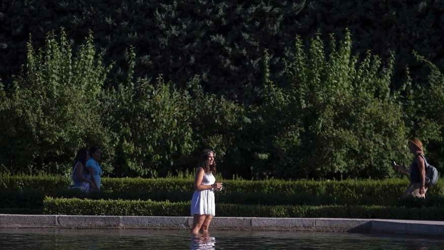A woman cools off in a park pond in Madrid, Spain, Thursday, July 9, 2015.  Spain has been in a heat wave for nearly two weeks, with temperatures reaching 40 C (104 F). The heatwave is expected to last around another week. (AP Photo/Paul White)