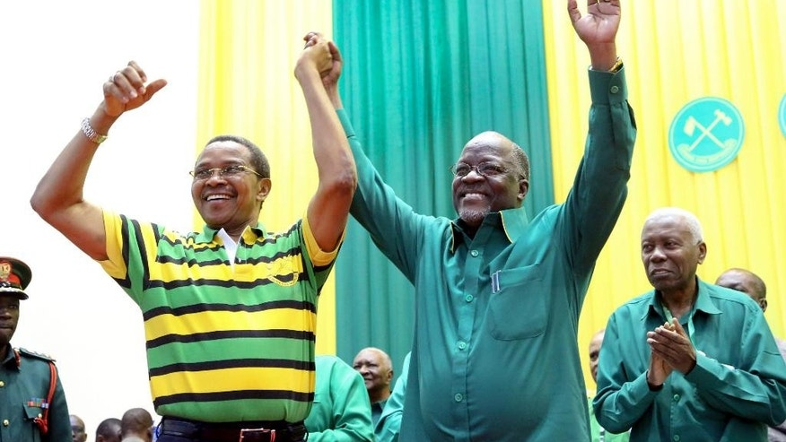 Tanzania's public works minister John Pombe Magufuli, right, celebrates with president Jakaya Kikwete, left, after the ruling party announced its presidential candidate, in Dodoma, Tanzania, Sunday, July 12, 2015. Tanzania's ruling party, which has been in power for five decades, has chosen public works minister John Pombe Magufuli as its presidential candidate, making him the favorite to replace current president Jakaya Kikwete in the upcoming October election. (AP Photo/Khalfan Said)