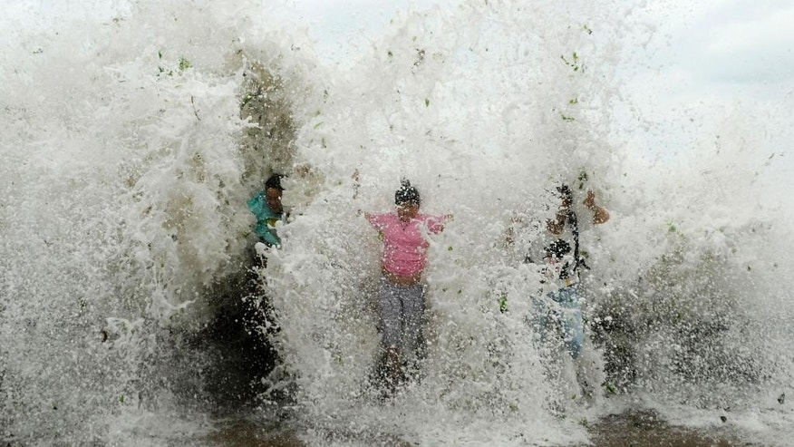 People are splashed by sea waves strengthened by Typhoon Chan-hom at the seacoast of Qingdao in east China's Shandong province Sunday, July 12, 2015. The typhoon pounded the Chinese coast south of Shanghai on Saturday with strong winds and heavy rainfall, submerging roads, felling trees and forcing the evacuation of people.  (Chinatopix via AP) CHINA OUT