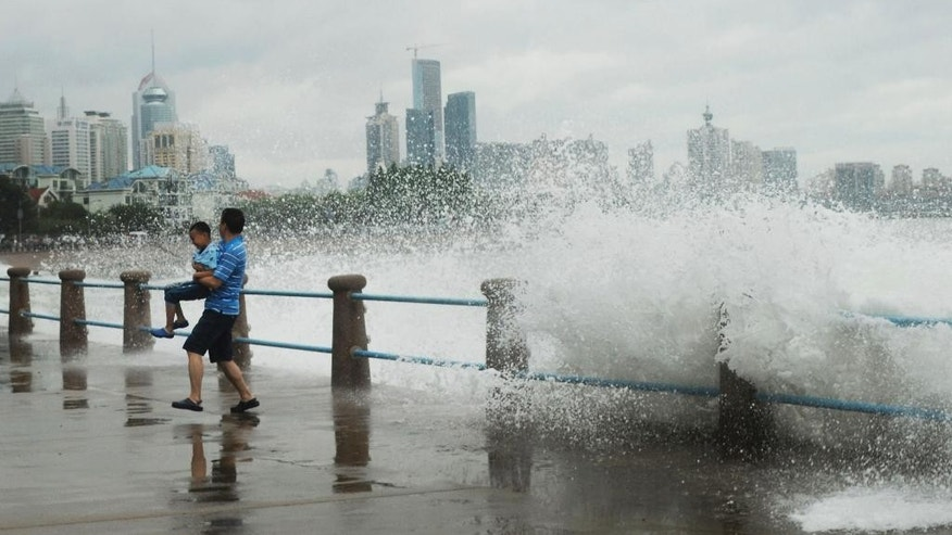 A man carrying a child runs away from massive waves hit the seacoast of Qingdao in east China's Shandong province Sunday, July 12, 2015. A typhoon pounded the Chinese coast south of Shanghai on Saturday with strong winds and heavy rainfall, submerging roads, felling trees and forcing the evacuation of people.  (Chinatopix via AP) CHINA OUT