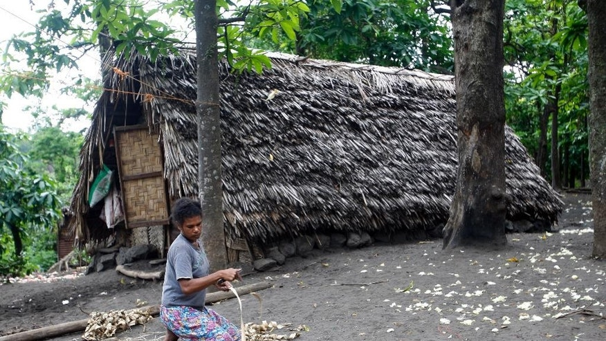 In this Tuesday, June 2, 2015, photo, a woman weaves a mat in a village on Tanna Island in Vanuatu. Tanna Island was particularly hard hit by Cyclone Pam, which struck in March. Many people in Vanuatu believe the cyclone was the latest manifestation of climate change. (AP Photo/Nick Perry)