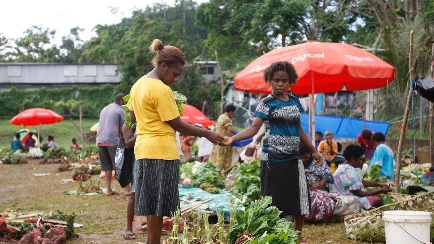 In this Saturday, May 30, 2015, photo, people shop at an outdoor market in Port Vila, Vanuatu. Many people in Vanuatu believe the nation is suffering the effects of climate change, including changes to crop seasons. (AP Photo/Nick Perry)