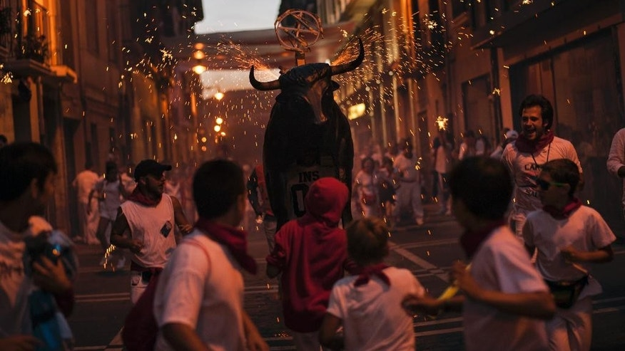 People run in front of fire bull in one old street of  city, at the San Fermin Festival, in Pamplona, Spain, Sunday, July 12, 2015. Revelers from around the world arrive to Pamplona every year to take part in some of the eight days of the running of the bulls. (AP Photo/Alvaro Barrientos)