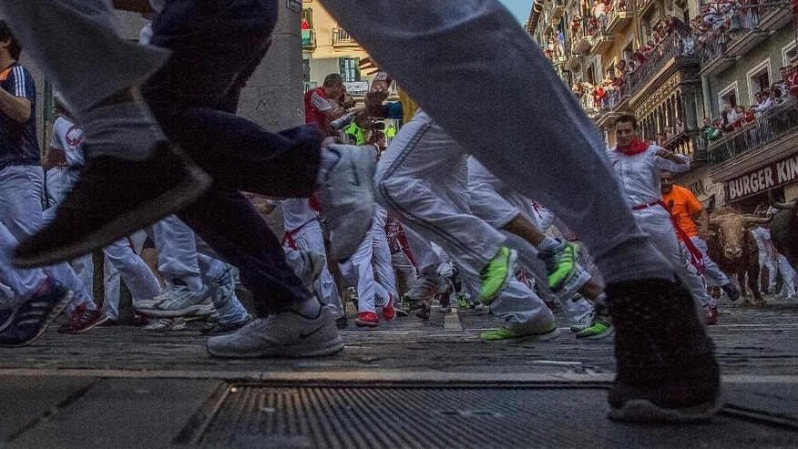 A Garcigrande fighting bull runs after revelers during the running of the bulls at the San Fermin festival in Pamplona, Spain, Monday, July 13, 2015. Revelers from around the world arrive to Pamplona every year to take part in some of the eight days of the running of the bulls. (AP Photo/Andres Kudacki)