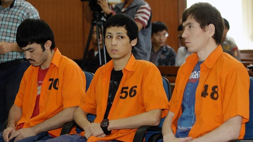 Suspected Islamic militants, from left to right, Abdulbasit Tuzer, Ahmet Mahmud and Abdullah sit on the defendant's chairs during their trial hearing at North Jakarta District Court in Jakarta, Indonesia, Monday, July 13, 2015. The court has sentenced the men believed to be members of China's ethnic Uighur minority community to six years in jail for conspiring with Indonesian terrorists. (AP Photo/Achmad Ibrahim)
