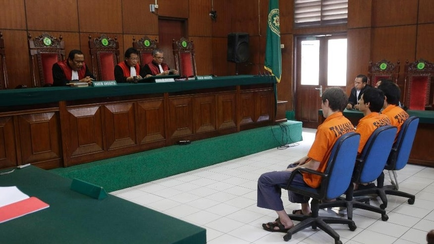 Presiding Judge Kun Marioso, second from left, reads the verdict of suspected Islamic militants Abdulbasit Tuzer, Abdullah and Ahmet Mahmud during their trial hearing at North Jakarta District Court in Jakarta, Indonesia, Monday, July 13, 2015. The court has sentenced the men believed to be members of China's ethnic Uighur minority community to six years in jail for conspiring with Indonesian terrorists. (AP Photo/Achmad Ibrahim)