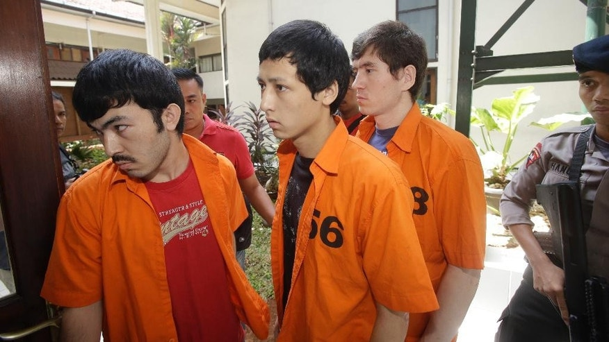 Suspected Islamic militants, from left to right, Abdulbasit Tuzer, Ahmet Mahmud and Abdullah are escorted by police officers prior to their trial hearing at North Jakarta District Court in Jakarta, Indonesia, Monday, July 13, 2015. The court has sentenced the men believed to be members of China's ethnic Uighur minority community to six years in jail for conspiring with Indonesian terrorists. (AP Photo/Achmad Ibrahim)