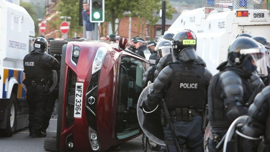 Police next to a car that was overturned on the Crumlin Road, Belfast Monday ,July 13, 2015, during the annual Twelfth of July celebrations, marking the victory of King William III's forces over James II at the Battle of the Boyne in 1690. (Brian Lawless/PA via AP) UNITED KINGDOM OUT  NO SALES  NO ARCHIVE