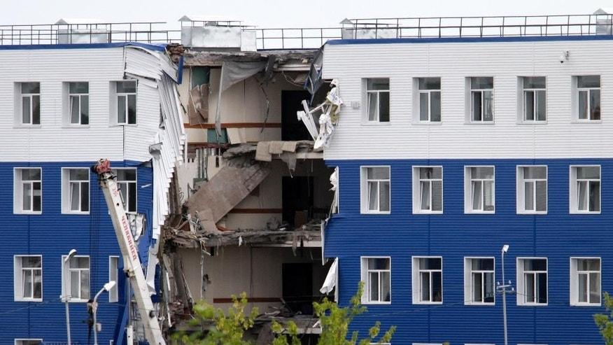 A military barrack with collapsed ceiling is seen at a base in Omsk, Russia, Monday, July 13, 2015. The ceiling collapsed Monday, causing four stories to crumble. Rescuers searched for hours for victims trapped under the debris of an airborne troops training center following the collapse that occurred in the early hours of the morning. (AP Photo/Dmitry Feoktistov)