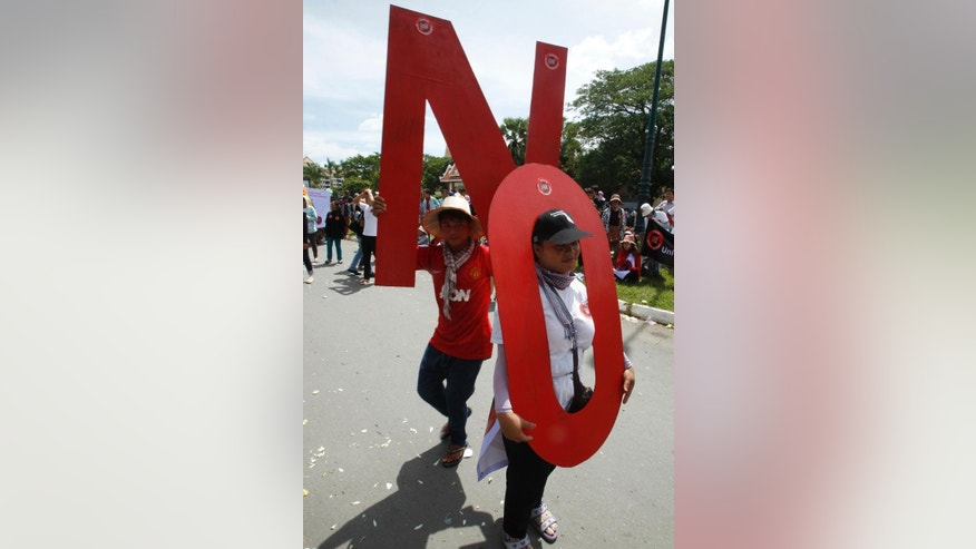 "Protesters carrying ""No"" signs march towards the National Assembly in Phnom Penh, Cambodia, Monday, July 13, 2015. Lawmakers of the ruling Cambodian People's Party approved a controversial draft law Monday that critics say gives authorities sweeping powers to crack down on civil society groups that challenge the government. The Law on Associations and Non-Governmental Organizations tightly regulates all non-governmental organizations in the country and grants the government sweeping powers to clamp down on civil society activities it deems to be a threat to national security. (AP Photo/Heng Sinith)"