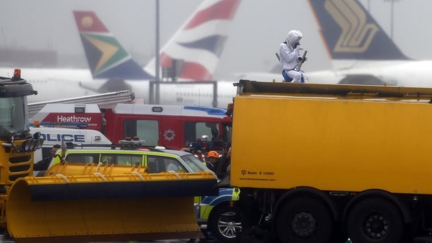Emergency service workers talk to an activist, dressed as a teddy bear, top right, from the pressure group Plane Stupid, who was one of several demonstrators who occupied the north runway at London's Heathrow Airport to launch a protest Monday July 13, 2015. A spokesman for the action group said a dozen demonstrators cut through a fence and entered the runway early on Monday. (Steve Parsons/PA via AP) UNITED KINGDOM OUT