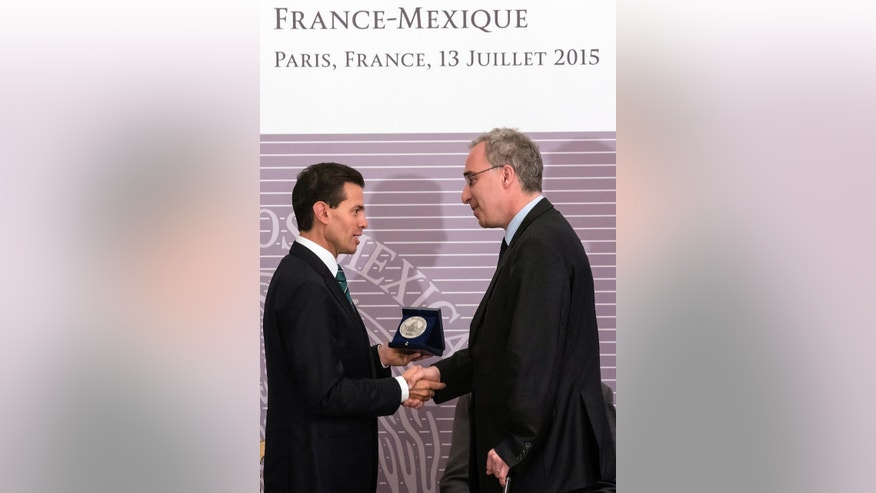 Mexico's President Enrique Pena Nieto, left shakes hand with French Rector of the Paris Academy Francois Weil, as they attend a meeting at the French-Mexican Academic and Scientific partnership headquarters in Paris, France, Monday, July 13, 2015. Pena Nieto is in France for a four-day visit. (AP Photo/Kamil Zihnioglu)