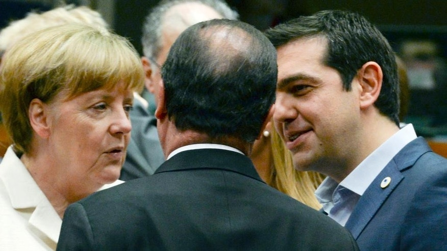 German Chancellor Angela Merkel, left, speaks with French President Francois Hollande, center, and Greek Prime Minister Alexis Tsipras during a meeting of eurozone heads of state at the EU Council building in Brussels on Sunday, July 12, 2015. Skeptical European creditors raced Sunday to narrow differences both among themselves and with Athens, aiming to come up with a tentative agreement to stave off an immediate financial collapse in Greece that would reverberate across the continent. (AP Photo)