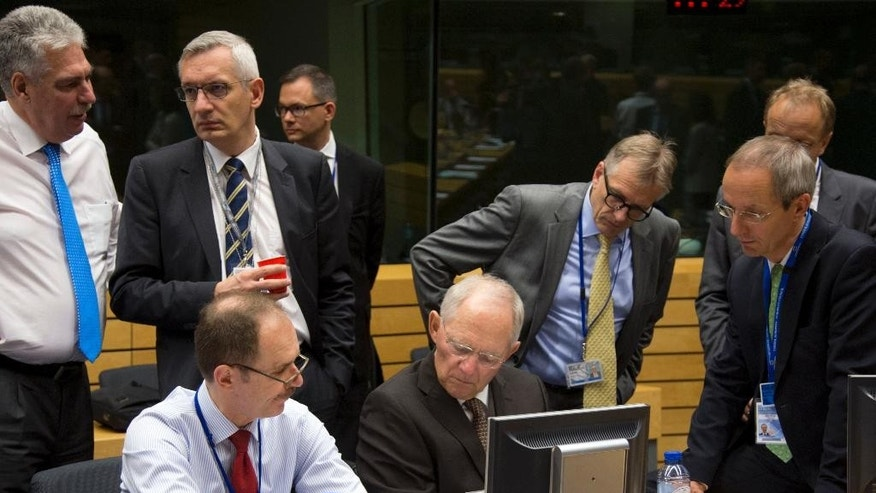 German Finance Minister Wolfgang Schaeuble, sitting center, goes over papers with members of his delegation during a round table meeting of eurogroup finance ministers at the EU Lex building in Brussels on Sunday, July 12, 2015. Greece has another chance Sunday to convince skeptical European creditors that it can be trusted to enact wide-ranging economic reforms which would safeguard its future in the common euro currency. (AP Photo/Virginia Mayo)