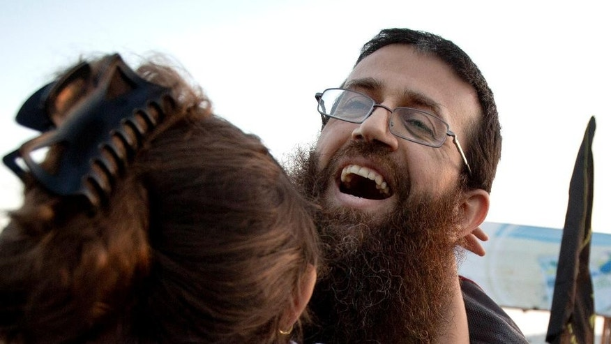 FILE - In this Sunday, July 12, 2015 file photo, Palestinian Khader Adnan hugs his daughter after his release from an Israeli prison in the West Bank village of Arrabeh near Jenin. Israeli police said they have detained Adnan again, just a day after he was released from Israeli custody. Police said Adnan was detained Monday in Jerusalem's Old City because he didn't have an Israeli permit to be in the area. He was detained as throngs of Muslim worshippers were visiting Jerusalem for a Muslim holy night. (AP Photo/Majdi Mohammed, File)