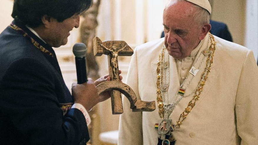 "In this Wednesday, July 8, 2015 photo, Bolivian President Evo Morales presents Pope Francis with a crucifix carved into a wooden hammer and sickle, in La Paz, Bolivia. The crucifix is a replica, originally designed by Jesuit activist Luis Espinal, who was assassinated in 1980 by suspected paramilitaries during the months that preceded a military coup. Even though the Vatican was not expecting the unusual gift, it is seeking to explain the ""Communist crucifix"" given to Francis, saying it's a symbol of dialogue and not an offensive melding of faith and ideology. (L'Osservatore Romano/Pool Photo via AP)"