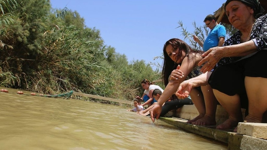 In this July 6, 2015 photo, Jordanian Christians pour water over themselves at the baptismal area on the eastern bank of the Jordan River in South Shuna, Jordan. UNESCO recently designated Jordan's baptismal area a World Heritage site, over the Israeli-run site of Qasr al-Yahud in the West Bank, which is one of three territories captured by Israel in the 1967 Mideast war, and the baptism site of Qasr al-Yahud remains under full Israeli military occupation. (AP Photo/Raad Adayleh)
