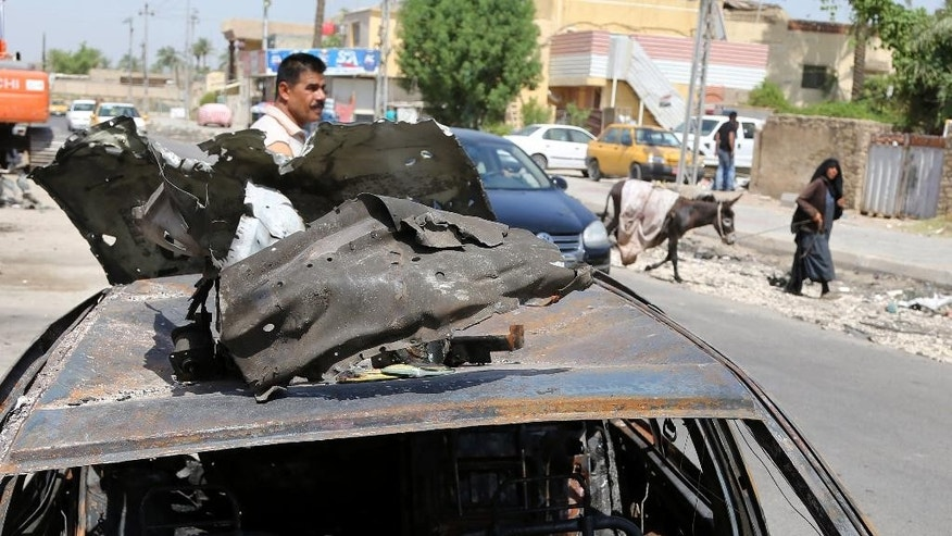 People inspect the scene of after an explosion hit a busy commercial area in Baghdad, Iraq Monday, July 13, 2015. A string of car bombs and explosive belts attacks across Baghdad killed and wounded dozens of people on Sunday, Iraqi officials said. (AP Photo/Karim Kadim)