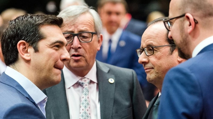 Greek Prime Minister Alexis Tsipras, left, speaks with, from left, European Commission President Jean-Claude Juncker, French President Francois Hollande and Belgian Prime Minister Charles Michel during a meeting of eurozone heads of state at the EU Council building in Brussels on Sunday, July 12, 2015. Skeptical European creditors raced Sunday to narrow differences both among themselves and with Athens, aiming to come up with a tentative agreement to stave off an immediate financial collapse in Greece that would reverberate across the continent. (AP Photo/Geert Vanden Wijngaert)