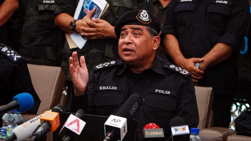File-This file photo of May 25, 2015, shows Malaysian National Police Chief Khalid Abu Bakar speaking at press conference in Wang Kelian, Malaysia. Malaysian police say they are investigating the leak of confidential documents that allegedly show millions of dollars were funneled to Prime Minister Najib Razak's account. (AP Photo/Joshua Paul, File)
