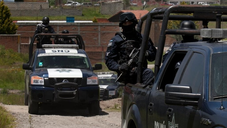 "Federal Police stand guard near a half-built house near the Altiplano maximum security prison in Almoloya, west of Mexico City, Monday, July 13, 2015. A widespread manhunt that included highway checkpoints, stepped up border security and closure of an international airport failed to turn up any trace of Mexican drug kingpin Joaquin ""El Chapo"" Guzman by Monday, more than 24 hours after he escaped through an underground tunnel leading from his Altiplano prison cell's shower area. (AP Photo/Marco Ugarte)"