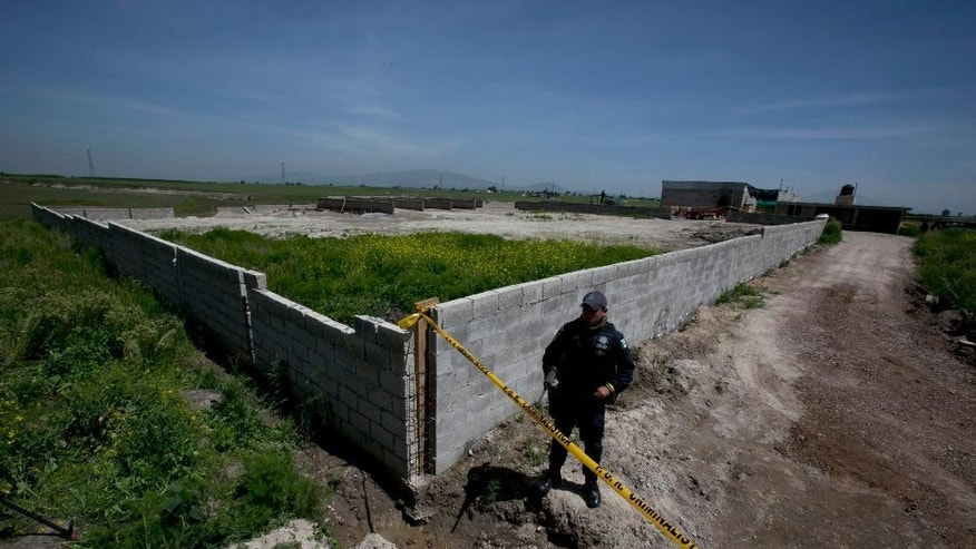 "A Federal Police officer stands guard on the perimeters of a half-built house near the Altiplano maximum security prison in Almoloya, west of Mexico City, Monday, July 13, 2015. A widespread manhunt that included highway checkpoints, stepped up border security and closure of an international airport failed to turn up any trace of Mexican drug kingpin Joaquin ""El Chapo"" Guzman by Monday, more than 24 hours after he escaped through an underground tunnel in his Altiplano prison cell. (AP Photo/Marco Ugarte)"
