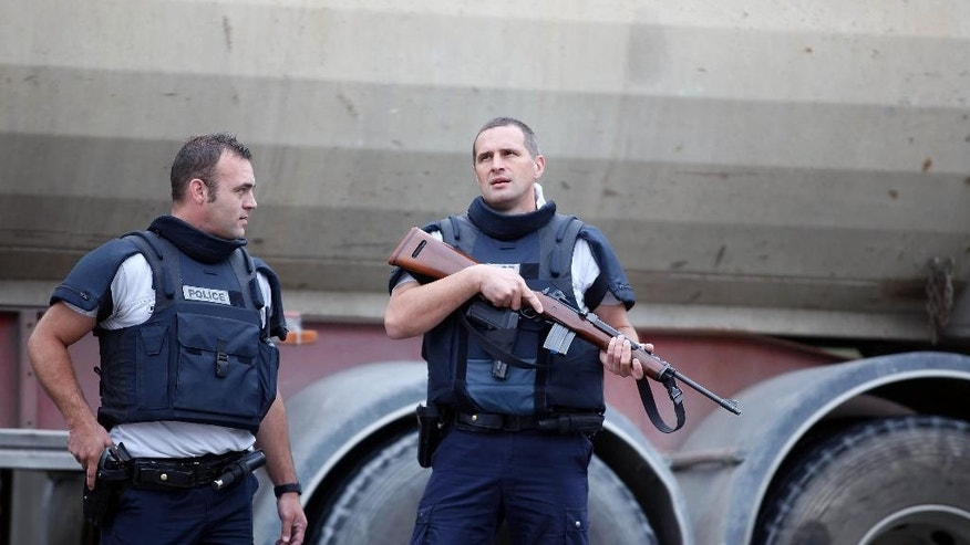 Police riot officers stand outside a suburban clothing store, in Villeneuve-la-Garenne, north of Paris, Monday, July 13, 2015. A group of assailants broke into a discount clothing store near Paris on Monday, trapping 18 people inside for hours before fleeing and prompting a manhunt throughout the area, police said. (AP Photo/Thibault Camus)