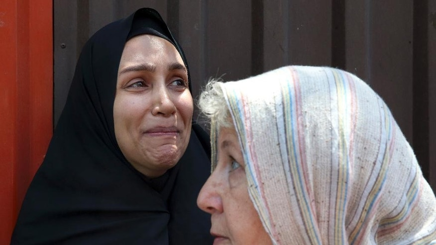 Mary Rezaian, mother of detained Washington Post correspondent Jason Rezaian, speaks with the media as Jason's wife Yeganeh weeps, after a hearing at the Revolutionary Court in Tehran, Iran, Monday, July 13, 2015. The closed-door trial of detained Rezaian, who has been detained in an Iranian prison for nearly a year, ended Monday after a third session, Iran's official IRNA news agency reported. Rezaian, 39, is being tried in a Revolutionary Court on charges including espionage and distributing propaganda against the Islamic Republic. U.S. officials, the Post and rights groups have criticized his trial and pressed for his release. (AP Photo/Vahid Salemi)