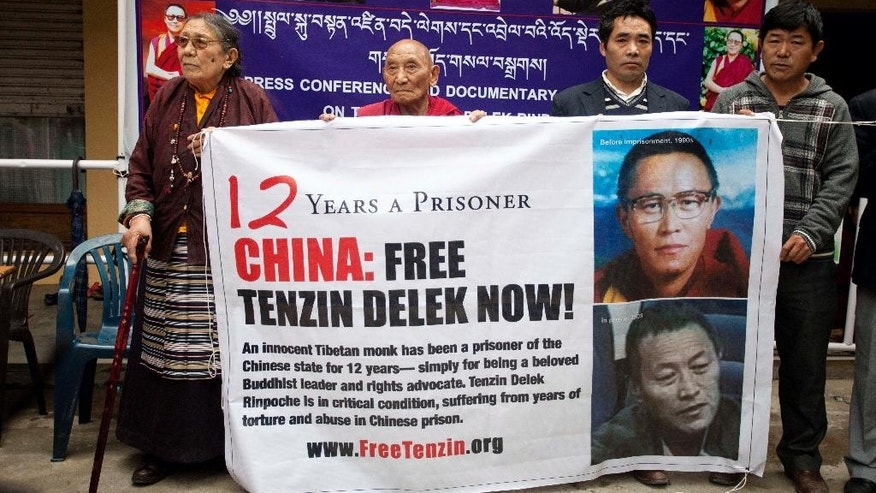 FILE - In this April 7, 2014 file photo, exile Tibetans hold a banner to demand the release of a Tibetan Buddhist leader Tenzin Delek Rinpoche, who has been in a Chinese prison since 2002, during a protest in Dharmsala, India. Tibetan lama Tenzin Delek Rinpoche has died in prison 13 years into serving a sentence for what human rights groups say were false charges that he was involved in a bombing in a public park. He was 65. Relatives were informed of the death Sunday, July 12, 2015, New York-based Students for a Free Tibet said Monday, July 13. Police in Sichuan province in southwestern China confirmed the death but declined to give further details. (AP Photo/Ashwini Bhatia, File)