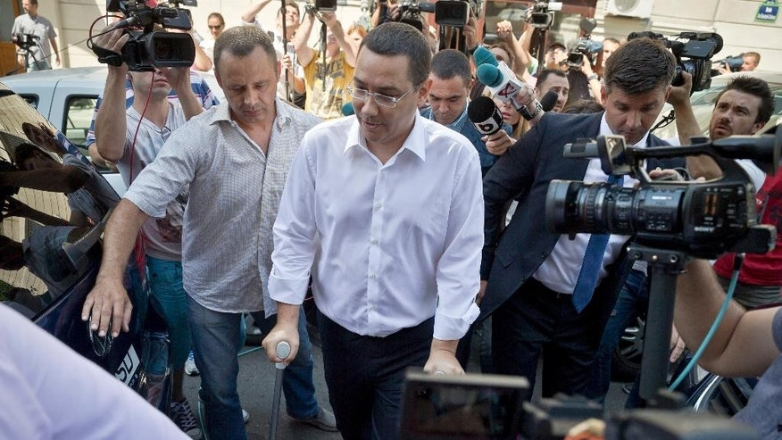 Romanian Premier Victor Ponta leaves  the national anti-corruption prosecutors office after being questioned, in Bucharest, Romania, Monday, July 13, 2015.  Romanian prosecutors indicted Prime Minister Victor Ponta on Monday as part of a wide-ranging corruption investigation. Prosecutors said Ponta has been indicted on charges including tax evasion, money laundering, conflict of interest and making false statements while he was working as a lawyer in 2007 and 2008. At the time, Ponta was a lawmaker. He denies wrongdoing.  (AP Photo/Vadim Ghirda)