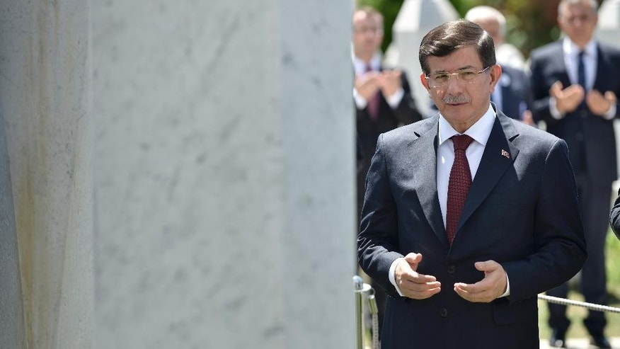 Turkish Prime Minister Ahmet Davutoglu pays respects at the grave of the first Bosnian president Alija Izetbegovic  in Sarajevo, Bosnia, Friday, July 10, 2015. Dvaoutoglu is in Bosnia for a two-day visit to mark the 20th anniversary of the Srebrenica massacre, the worst crime in Europe after the Nazi era, which will take place in Srebrenica on Saturday, July 11, 2015.(AP Photo/Sulejman Omerbasic)